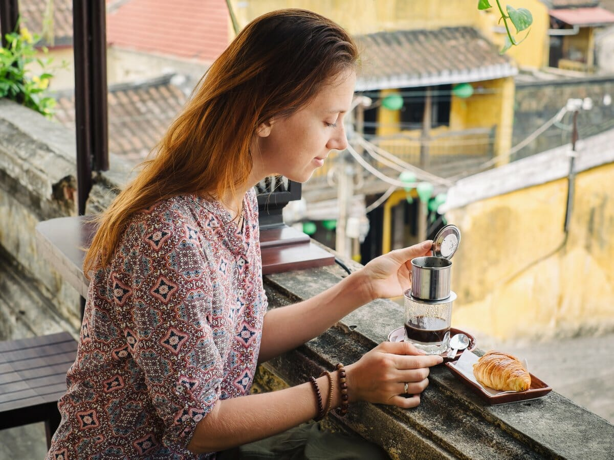 Best of Vietnam Tour gallery image of woman drinking Vietnamese coffee in Hoi An
